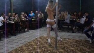 Una mujer ucraniana con medias blancas y bragas baila un striptease en un cheburechny en la orilla de Kirillovka