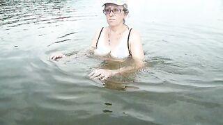 Esposa gorda de 50 años con gafas se baña en un estanque y muestra las tetas