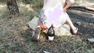Esbelta niña sentada en diferentes botellas en el bosque con una vagina y anal