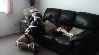 Mujer de látex atada tratando de liberarse con los ojos vendados