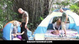 Los papás tienen las hijas del otro en un picnic en la naturaleza.