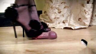 Amante en zapatos de tacón alto frota la polla del esclavo que sobresale de la mesa