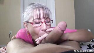 Una anciana canosa con gafas chupa la polla de una joven amiga de su esposo
