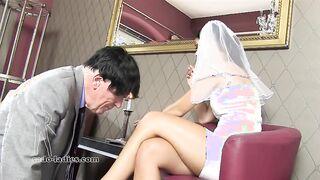 La novia empuja al viejo marido y lo obliga a besarle las piernas.